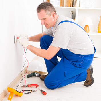 Installateur, der den Leistungspegel einer Steckdose in einem Haus prüft
